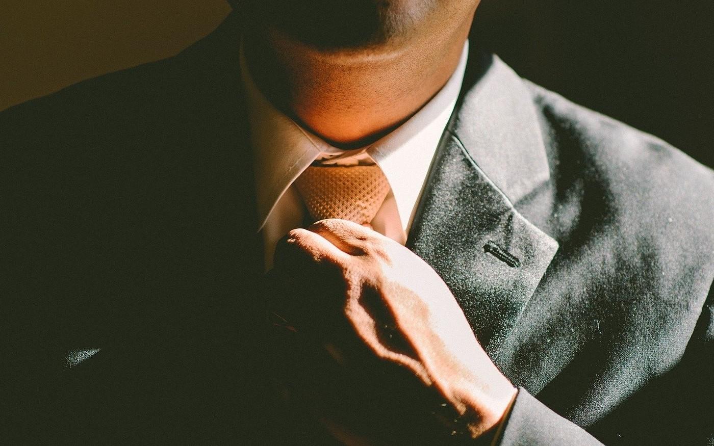 Man tightens neck tie before starting work